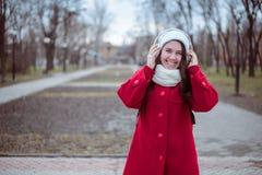 Retrato de una música que escucha de la muchacha feliz en línea con los auriculares inalámbricos de un smartphone en sombrero Fotos de archivo