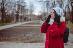 Retrato de una música que escucha de la muchacha feliz en línea con los auriculares inalámbricos de un smartphone en sombrero Fotografía de archivo