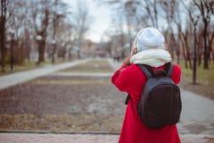 Retrato de una música que escucha de la muchacha feliz en línea con los auriculares inalámbricos de un smartphone en sombrero Foto de archivo libre de regalías