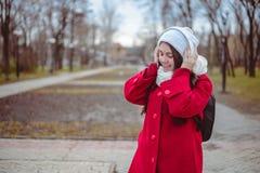 Retrato de una música que escucha de la muchacha feliz en línea con los auriculares inalámbricos de un smartphone en sombrero Imágenes de archivo libres de regalías
