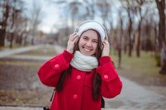 Retrato de una música que escucha de la muchacha feliz en línea con los auriculares inalámbricos de un smartphone en sombrero Foto de archivo