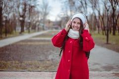 Retrato de una música que escucha de la muchacha feliz en línea con los auriculares inalámbricos de un smartphone en sombrero Imagen de archivo libre de regalías