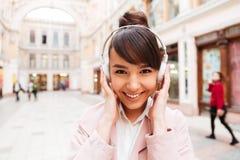 Retrato de una música que escucha sonriente de la muchacha linda con los auriculares Imagen de archivo libre de regalías