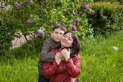 Retrato de una madre con su hijo adolescente en un jardín floreciente de la lila Imagen de archivo libre de regalías