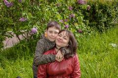 Retrato de una madre con su hijo adolescente en un jardín floreciente de la lila Foto de archivo