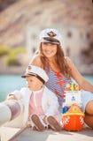 Retrato de una madre con su hijo que juega en el embarcadero por el mar en la ciudad, aún foto de la vida Fotos de archivo