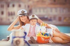 Retrato de una madre con su hijo que juega en el embarcadero por el mar en la ciudad, aún foto de la vida Imagen de archivo libre de regalías