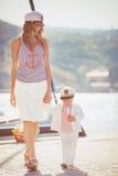 Retrato de una madre con su hijo que juega en el embarcadero por el mar en la ciudad, aún foto de la vida Imagen de archivo
