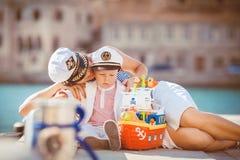 Retrato de una madre con su hijo que juega en el embarcadero por el mar en la ciudad, aún foto de la vida Fotografía de archivo