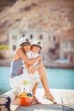 Retrato de una madre con su hijo que juega en el embarcadero por el mar en la ciudad, aún foto de la vida Foto de archivo libre de regalías