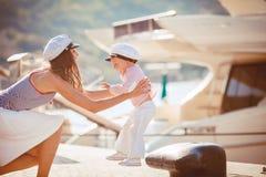 Retrato de una madre con su hijo que juega en el embarcadero por el mar en la ciudad, aún foto de la vida Imágenes de archivo libres de regalías
