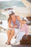 Retrato de una madre con su hijo que juega en el embarcadero por el mar en la ciudad, aún foto de la vida Foto de archivo