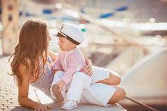 Retrato de una madre con su hijo que juega en el embarcadero por el mar en la ciudad, aún foto de la vida Imagenes de archivo