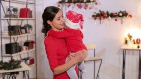 Retrato de una madre con un pequeño bebé recién nacido por días de fiesta de la Navidad en casa metrajes