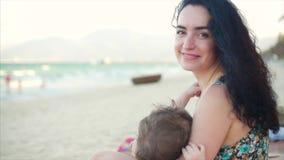 Retrato de una madre encantadora con un bebé en sus brazos La mamá con el bebé está gozando del aire fresco, mamá es amamantamien
