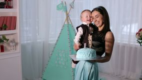 Retrato de una madre feliz con un hijo de un año en el cumpleaños con una torta almacen de video