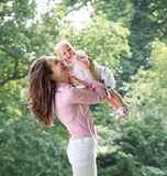 Retrato de una madre feliz que juega con el bebé en el parque Imágenes de archivo libres de regalías