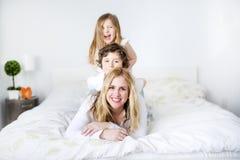 Retrato de una madre feliz y de sus niños que mienten en una cama Fotografía de archivo