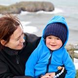 Retrato de una madre joven caucásica y de su niño con la playa de Torimbia en fondo en una mañana fría de pascua fotos de archivo