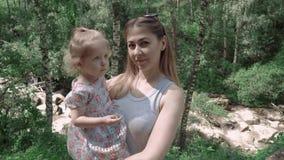 Retrato de una madre joven hermosa con su hija en el bosque, en un fondo de un río de la montaña, primer metrajes