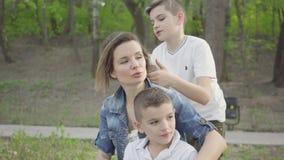Retrato de una madre joven linda con los ni?os adorables jovenes que descansan en el parque Reconstrucci?n al aire libre metrajes