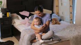 Retrato de una madre joven linda que abraza a su pequeño hijo en un dormitorio acogedor metrajes