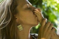 Retrato de una madre que besa a su bebé Fotos de archivo