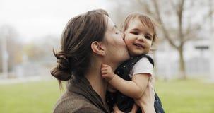 Retrato de una madre que besa a su bebé al aire libre almacen de video