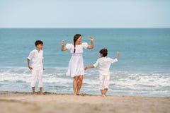 Retrato de una madre y de hijos alegres, felices en la playa Fotografía de archivo
