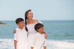 Retrato de una madre y de hijos alegres, felices en la playa Fotos de archivo libres de regalías