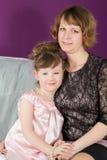 Retrato de una madre y de una hija joven en un cuarto púrpura Foto de archivo libre de regalías