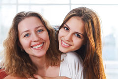 Retrato de una madre y una hija adolescente que están cercanas y un abrazo Fotografía de archivo libre de regalías