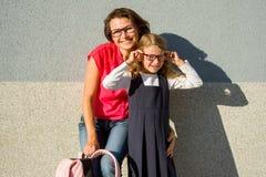 Retrato de una mamá y de una hija de una pequeña colegiala con Glasse imagenes de archivo