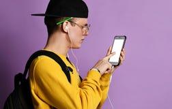 Retrato de una mochila que lleva del estudiante alegre, en casquillo y vidrios y smartphone con sobre fondo p?rpura imagenes de archivo