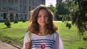 Retrato de una morenita caucásica sonriente de los jóvenes en el parque, universidad en el fondo almacen de metraje de vídeo
