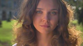 Retrato de una morenita caucásica triste joven en el parque, universidad en el fondo metrajes