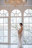Retrato de una morenita embarazada de la muchacha en dres transparentes blancos Imagen de archivo