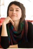 Retrato de una morenita hermosa joven en una bufanda rayada Imagen de archivo
