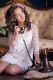 Retrato de una morenita joven con el teléfono retro Imagen de archivo