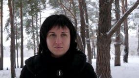 Retrato de una morenita joven en un abrigo de pieles, paseos en el bosque nevoso o el parque en un día frío y la mirada de la cám almacen de video