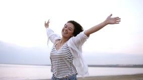 Retrato de una morenita rizada magnífica que corre feliz cerca del mar o del lago con las manos extendidas Casual blanco que llev almacen de video