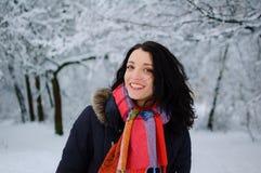 Retrato de una morenita sonriente joven en parque del invierno Foto de archivo
