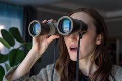 Retrato de una morenita sorprendida con los prismáticos que miran hacia fuera la ventana, espiando en vecinos Foto de archivo libre de regalías
