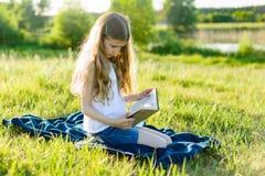 Retrato de una muchacha 8 años en prado verde El niño lee el libro, paisajes rústicos de la puesta del sol del fondo Fotos de archivo libres de regalías