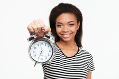 Retrato de una muchacha adolescente africana feliz que muestra el despertador Fotografía de archivo libre de regalías