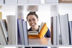 Retrato de una muchacha adolescente alegre en una biblioteca Ella es sonriente y de lectura de un libro anaranjado Fotos de archivo libres de regalías