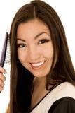 Retrato de una muchacha adolescente asiática joven linda que cepilla su pelo Imagen de archivo libre de regalías