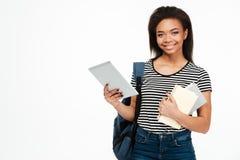Retrato de una muchacha adolescente con la mochila que sostiene la tableta de la PC Foto de archivo libre de regalías