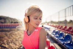 Retrato de una muchacha adolescente deportiva que descansa del ejercicio, escuchando la música con los auriculares, sonriendo al  Imágenes de archivo libres de regalías