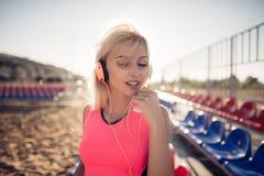 Retrato de una muchacha adolescente deportiva que descansa del ejercicio, escuchando la música con los auriculares, sonriendo al  Foto de archivo